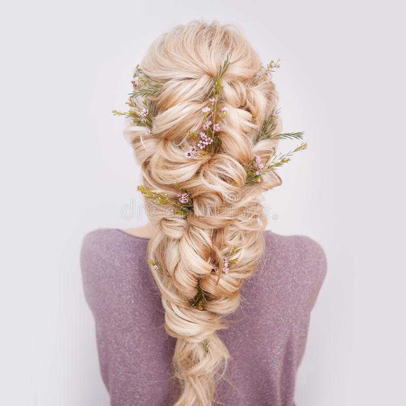 Back view of an elegant trendy hairstyle, interlacing curls and decorating with flower petals. Beautiful and well-groomed blonde hair royalty free stock image
