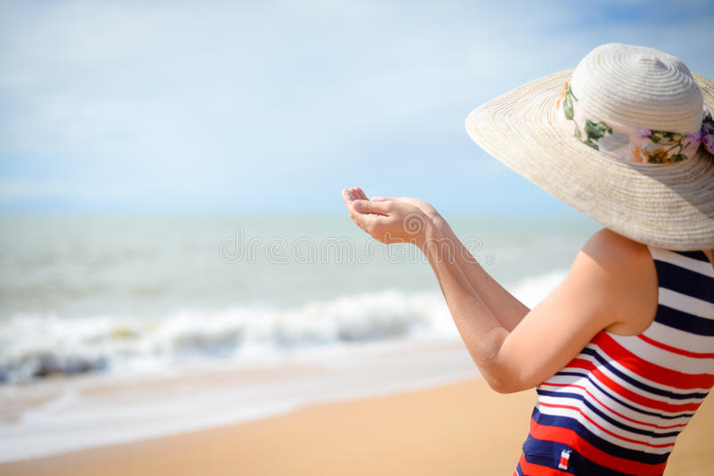 Back view of elegant woman holding hand palm up with summer sea on the background stock photo