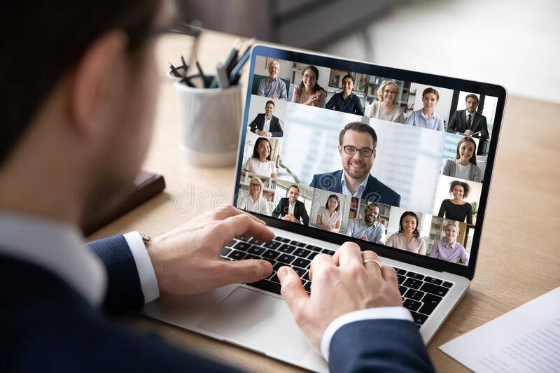 Back view of employee have online web conference with colleagues. Rear view of businessman speak on web conference with diverse colleagues using laptop Webcam stock photo