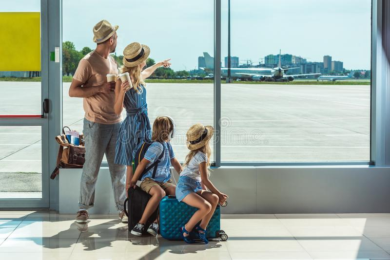 Family looking out window in airport royalty free stock photo