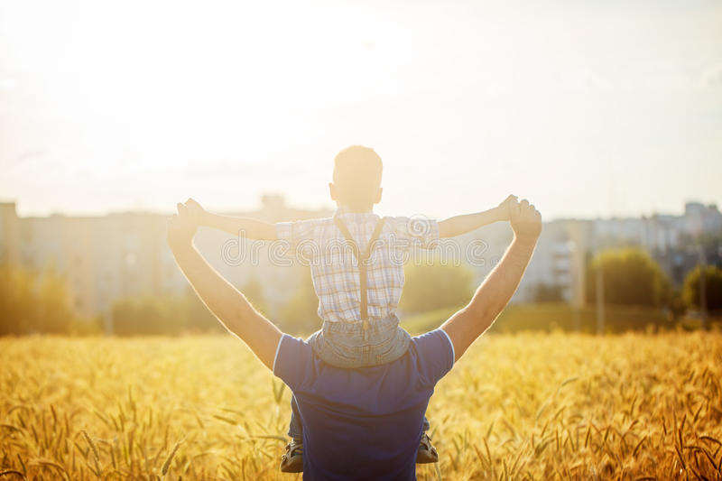 Back view of a father with his son on the shoulders standing in a field and city on summer sunset. Rear view of a father with his son on the shoulders standing royalty free stock photography