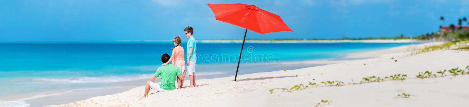 Father with kids at beach. Back view of father and kids enjoying beach vacation. Panorama perfect for banner stock image