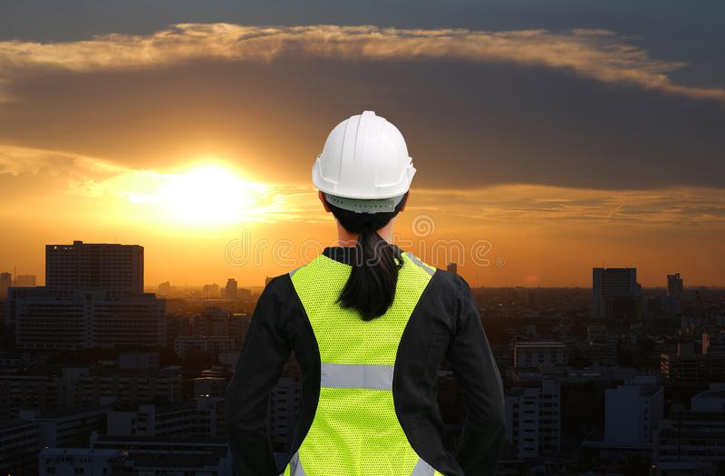 Back view of female construction worker against building at sunset in bangkok city background royalty free stock images