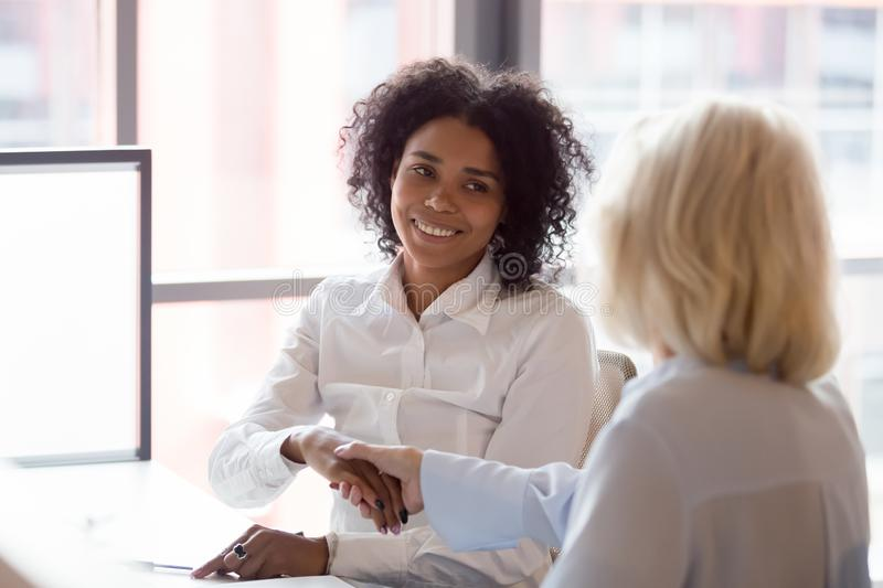 Smiling african American employee handshake colleague greeting at workplace stock photos
