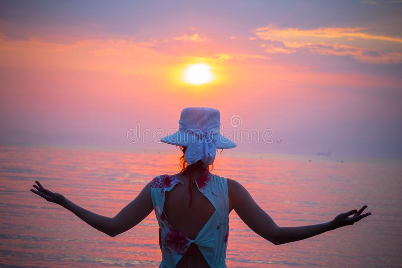 Back view of female enjoying the sunset over sea stock image