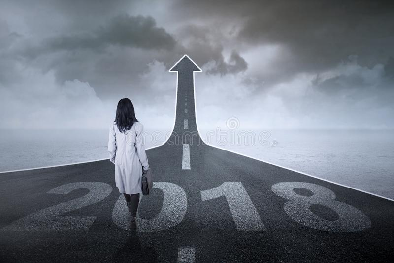 Female manager walking toward upward arrow. Back view of a female manager carrying a suitcase while walking toward end road shaped upward arrow with numbers 2018 stock photography