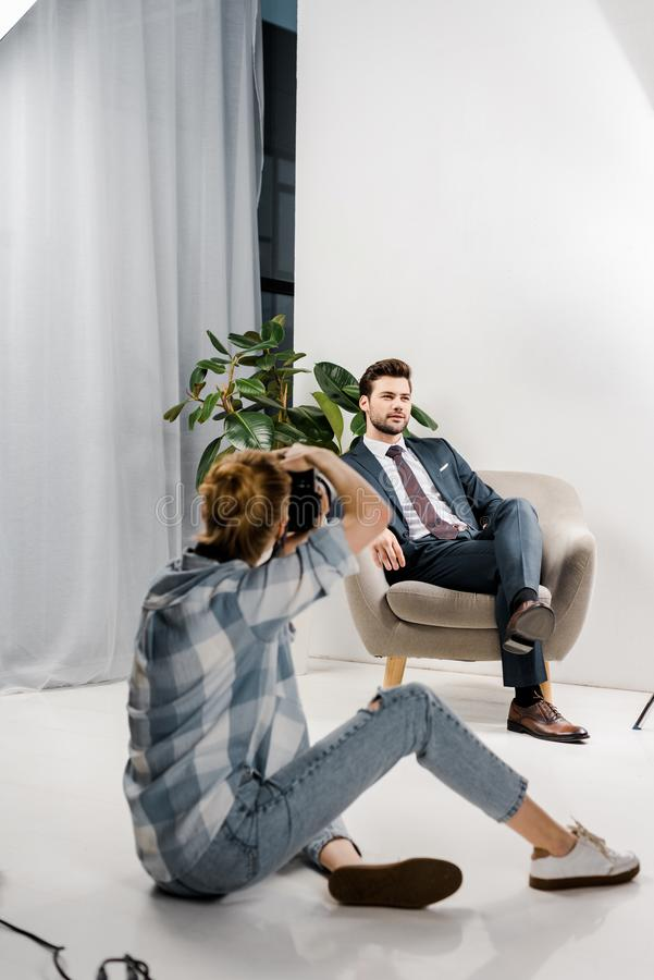 Back view of female photographer with camera photographing handsome male model. In studio stock photo