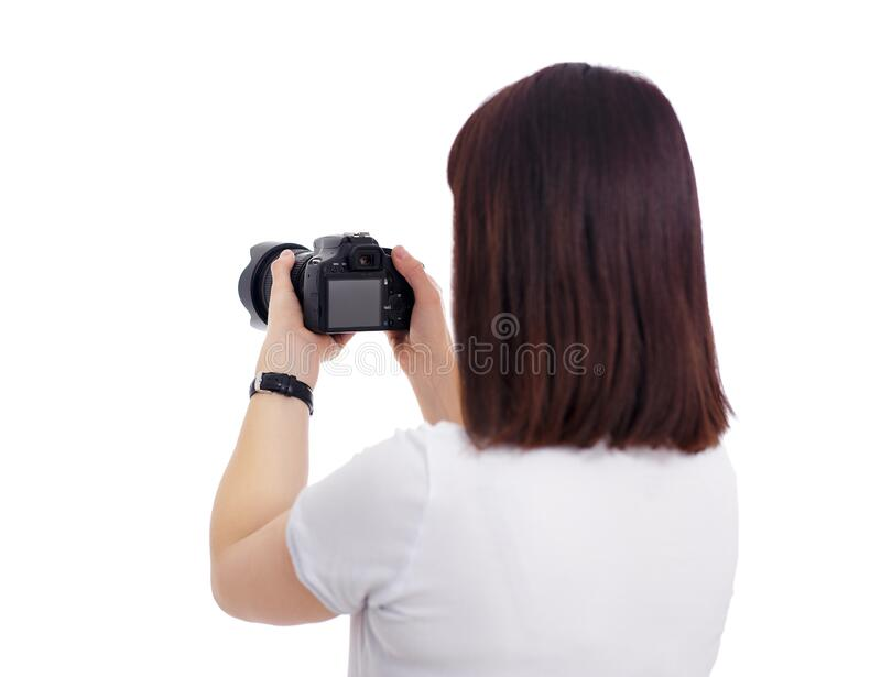 Back view of female photographer or videographer shooting video or photos on her camera isolated on white royalty free stock images