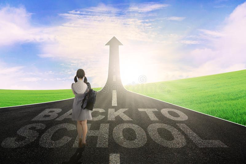 Female student with upward arrow. Back view of female student walking above text of back to school while looking at a road with upward arrow royalty free stock photo