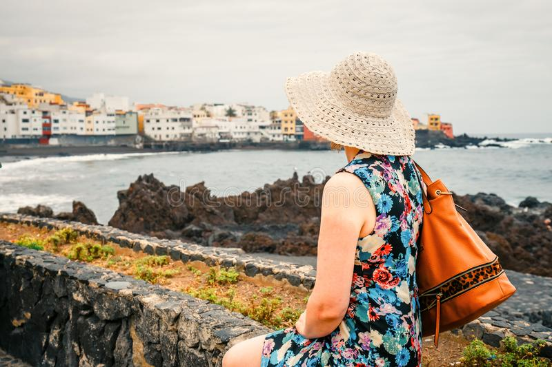 Female tourist with rucksack admires view of Puerto de la Cruz, Tenerife. Back view of female tourist with rucksack admires view of Puerto de la Cruz, Tenerife stock photography