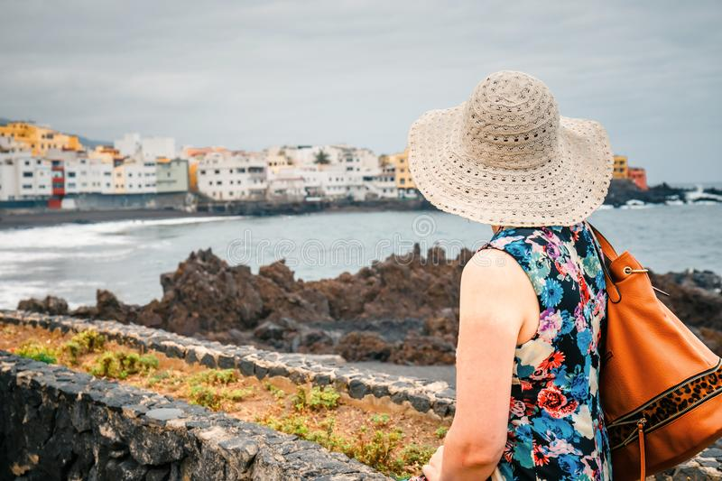 Back view of female tourist with rucksack admires view. Of Santa Cruz de Tenerife stock images