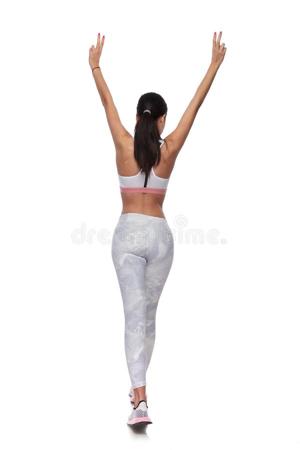 Back view of fit woman walking while making peace sign. Back view of fit woman walking on white background while making peace sign with both hands in the air royalty free stock photography