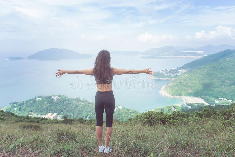 Back view of fitness woman standing on green mountain with her arms outstretched looking at sea landscape expressing royalty free stock photos