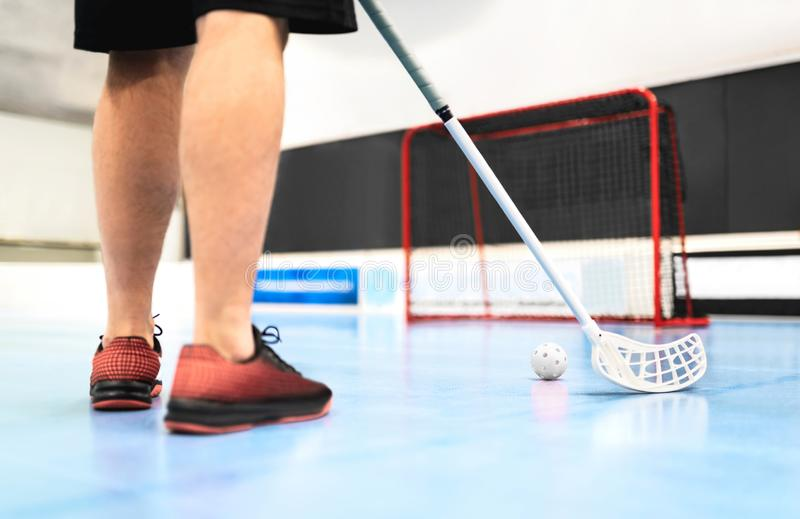 Back view of floorball player training with stick, ball and goal on court. royalty free stock photos
