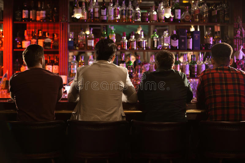 Back view of four young men drinking beer royalty free stock photos