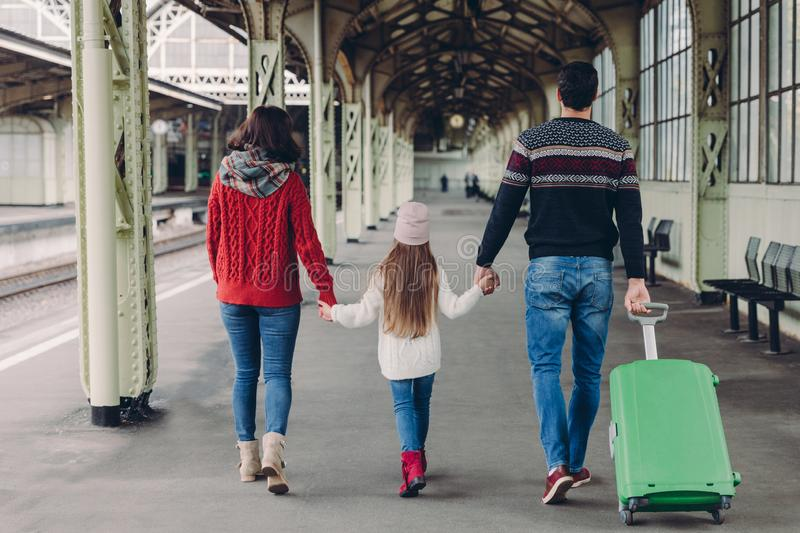 Back view of friendly family hold hands, carry suitcase, going to have voyage trip, pose on railway station platform. Young mother stock photos