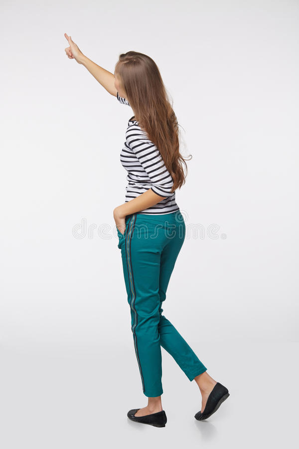 Back view of full length business woman in pointing at copy space, on gray background stock image