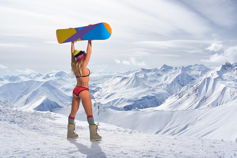 Back view of girl in bikini holding snowboard above head. Back view of unrecognizable blonde girl in bikini swimsuit with snowboard in outstretched arms above royalty free stock photos
