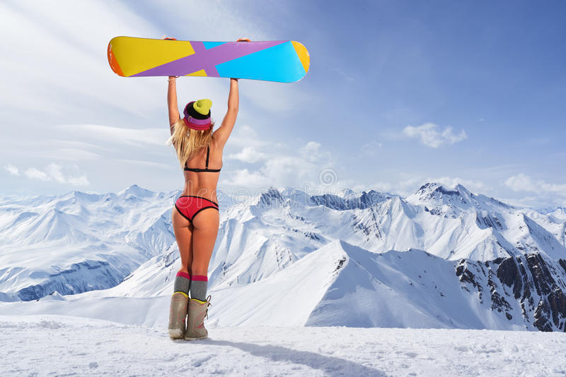 Back view of girl in bikini holding snowboard above head. Back view of unrecognizable blonde girl in bikini swimsuit with snowboard in outstretched arms above stock photography