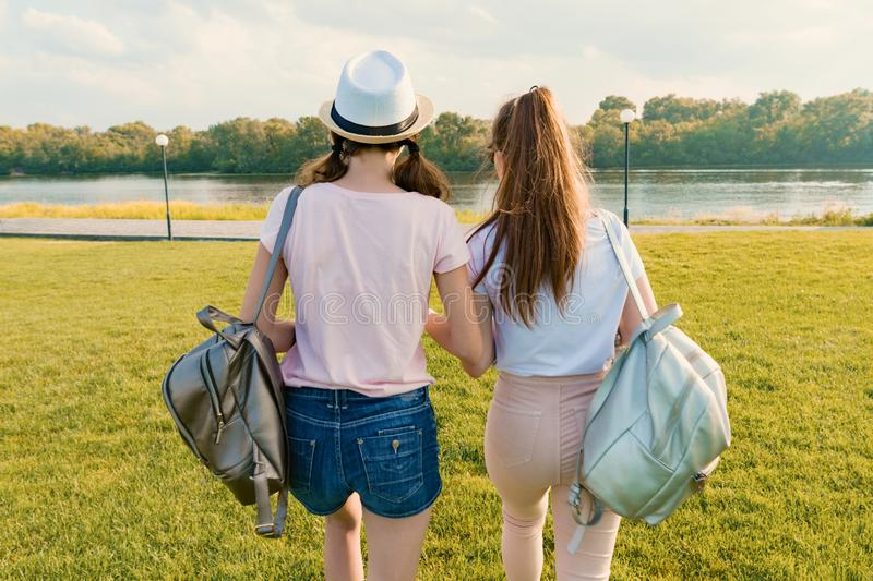 Back view, girl friends are walking in the park in nature. Girls walk along the green lawn, talk, have fun stock images