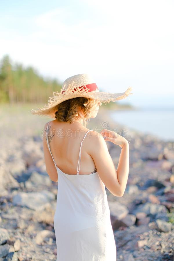 Back view of girl in hat walking on shingle beach. Back view of girl in hat with red ribbon walking on shingle beach. Concept of summer vacations and resort royalty free stock photo