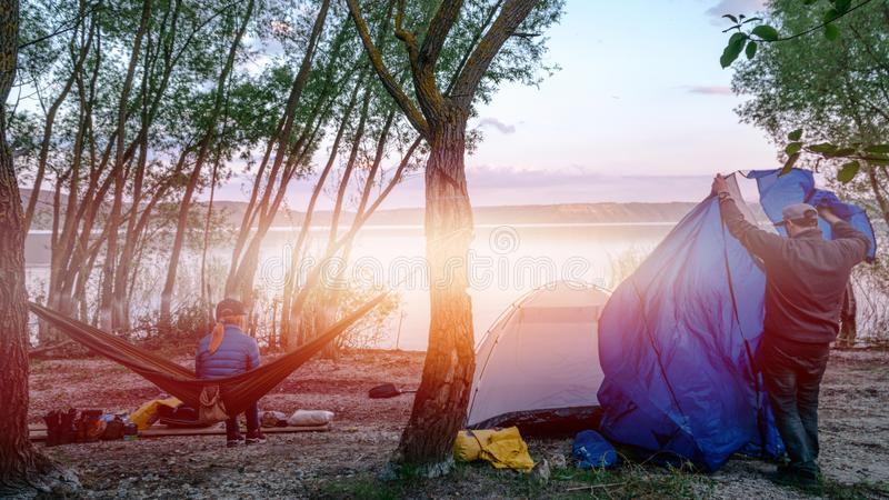 Back view of girl relaxing on olive hammock between two trees enjoying the view at the lake in summer evening a man sets up a tent royalty free stock photography