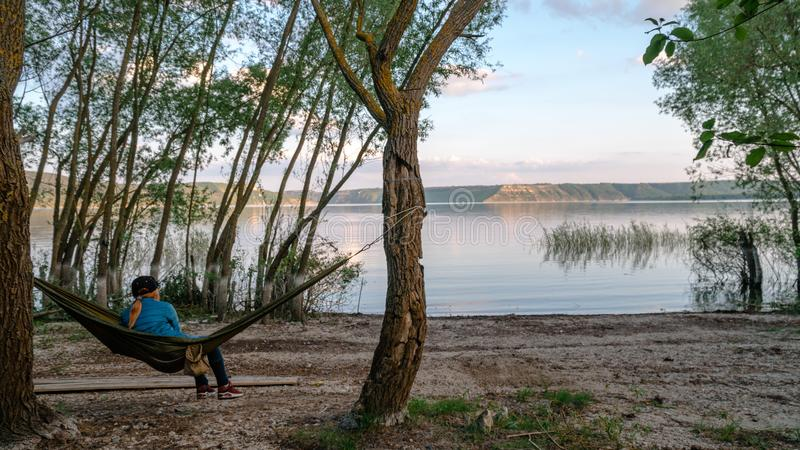 Back view of girl relaxing on olive hammock between two trees enjoying the view at the lake in summer morning. Copy space. Bakota royalty free stock photo