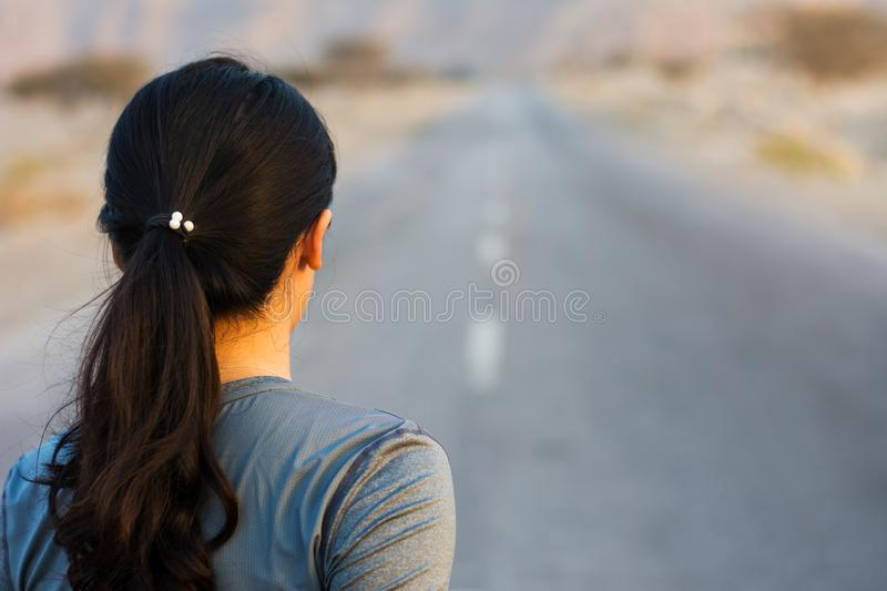 Back view of a Girl running on the road stock photo