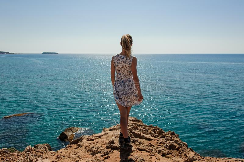 Back view girl standing on the rock in dress stock images
