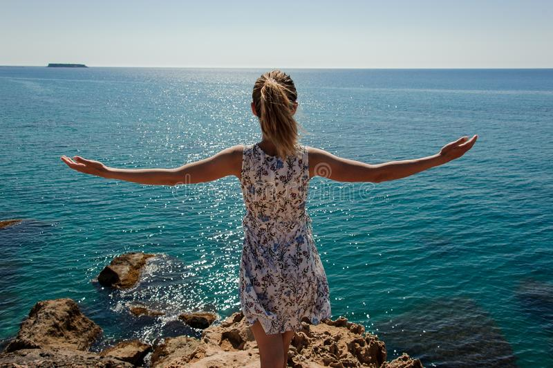 Back view girl standing on the rock in dress with a open hands stock photo