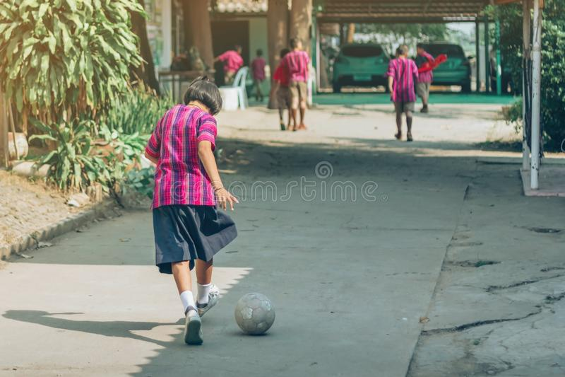 Back view of Girl student wear skirt to practice playing football alone on the street. In the school royalty free stock photo
