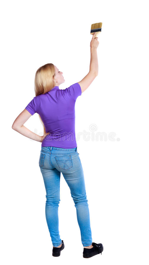 Back view of a girl who paints the paint roller. royalty free stock image