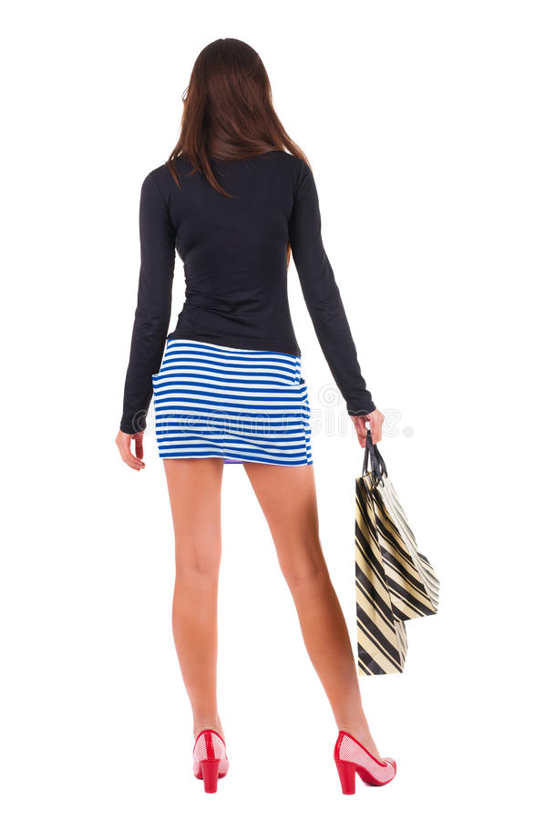 Back view of going woman in dress woman with shopping bags royalty free stock images
