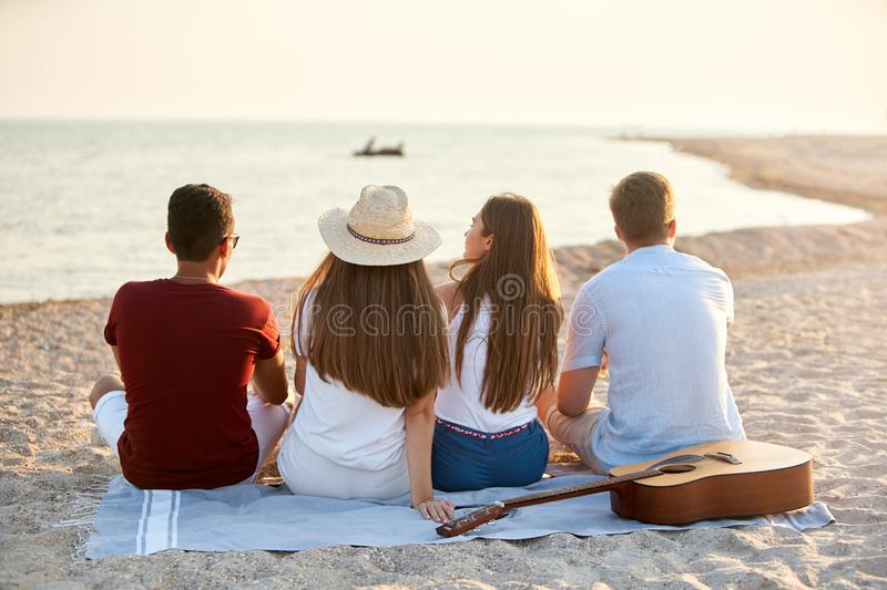 Back view of group of friends sitting together on towel on white sand beach during their vacation and enjoying a sunset royalty free stock photography