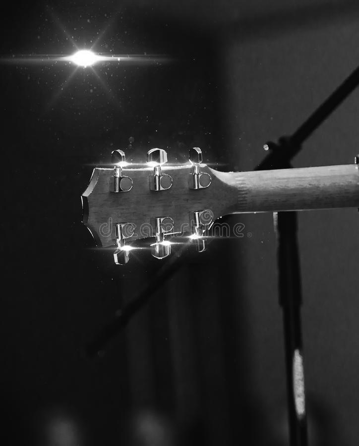 Back view of guitar headstock during spectacle in black & white color. Guitar headstock on concert stage background with hearts. Light flare effect. Best stock images