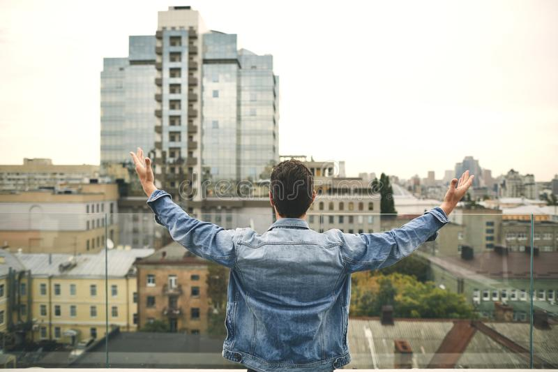 Young man in denim jacket is standing on terrace royalty free stock photos