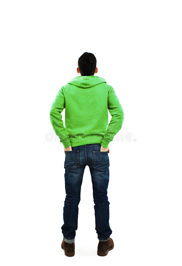 Back view of handsome with both hands in his pockets looking up stock photography