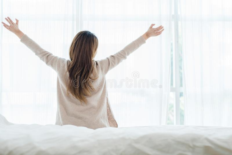 Back view of happy beautiful young Asian woman waking up in morning, sitting on bed, stretching in cozy bedroom. Back view of happy beautiful young Asian woman stock photography