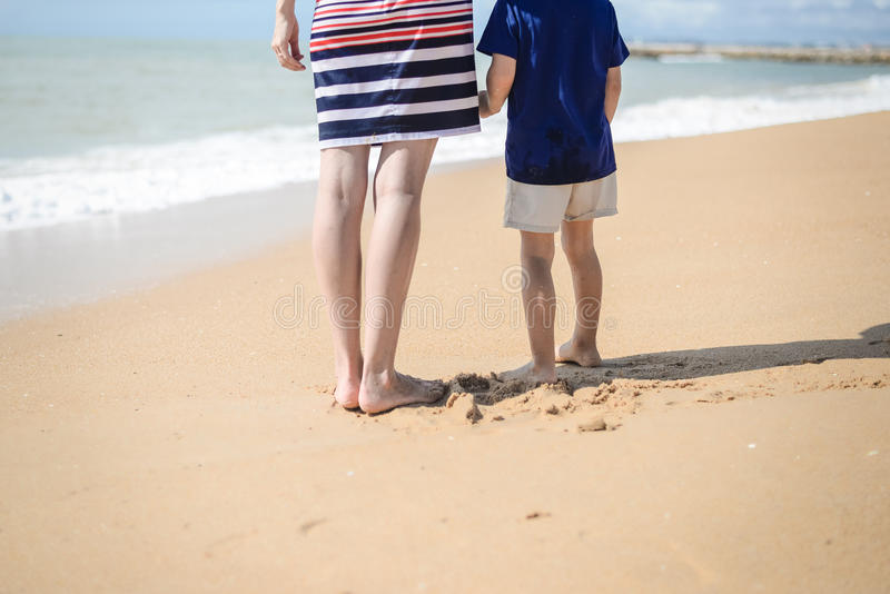 Back view of happy excited mother and kid have fun on beach on sunny outdoors stock images