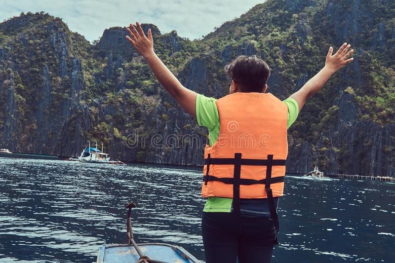 Back view of happy guy in a life jacket stands on a boat on the background of a beautiful landscape of rocky bay. royalty free stock images