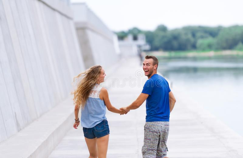 Back view of the happy loving couple holding hands and and to looking back royalty free stock photo