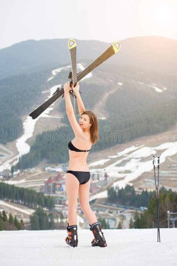 Back view of happy woman skier in swimsuit standing on the slope and holding skis above head stock photography