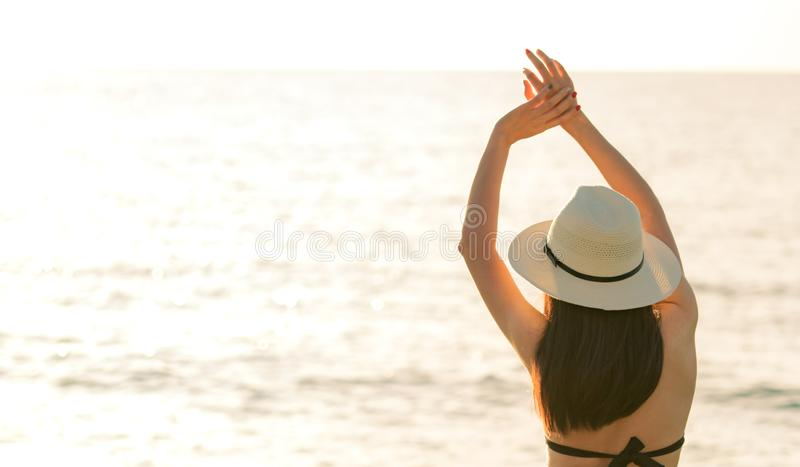 Back view of happy young Asian woman in black bikini and straw hat relax and enjoy at tropical paradise beach at sunset. Girl stock image