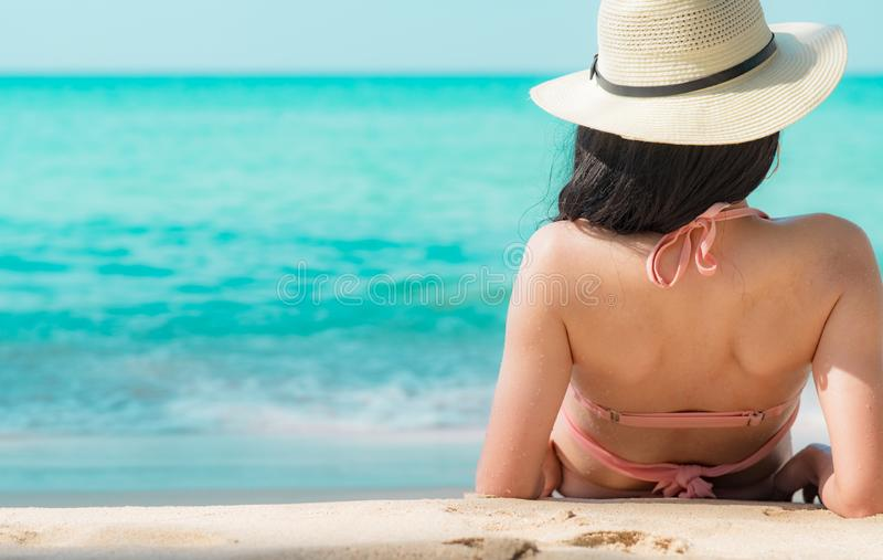Back view of happy young Asian woman in pink swimsuit and straw hat relax and enjoy holiday at tropical paradise beach at sunset. stock image