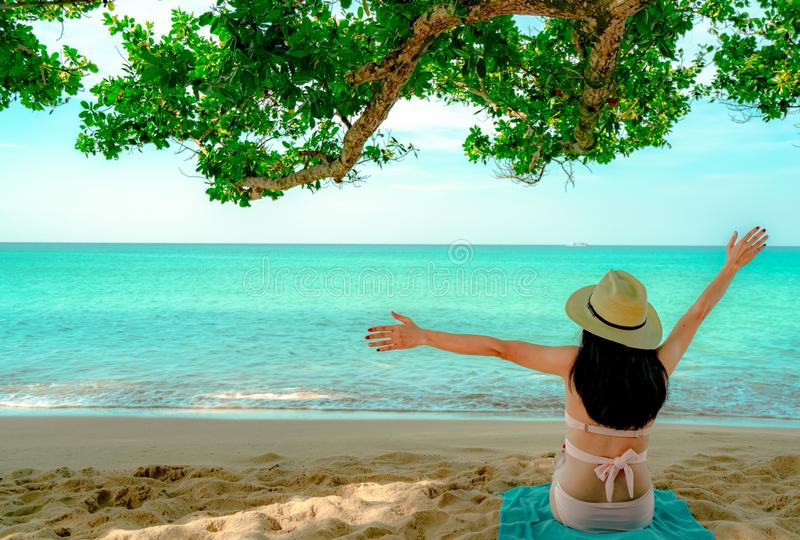 Back view of happy young Asian woman in pink swimsuit and straw hat relax and enjoy holiday at tropical sand beach under the tree stock photo