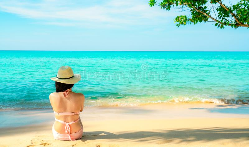 Back view of happy young Asian woman in pink swimsuit and straw hat relaxing and enjoy holiday at tropical paradise beach royalty free stock images