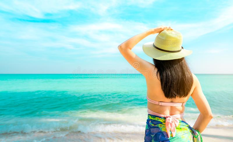 Back view of happy young Asian woman with straw hat relax and enjoy holiday at tropical paradise beach. Girl in summer vacation. Fashion. Beauty model. Sand royalty free stock images