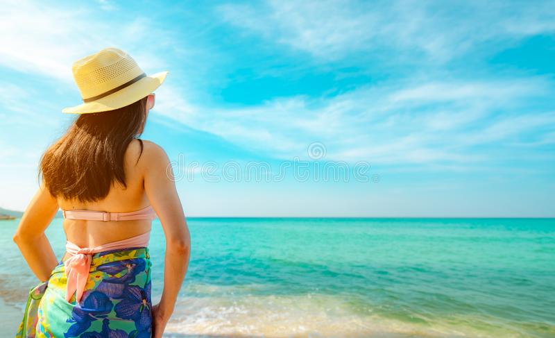 Back view of happy young Asian woman with straw hat relax and enjoy holiday at tropical paradise beach. Girl in summer vacation stock photo