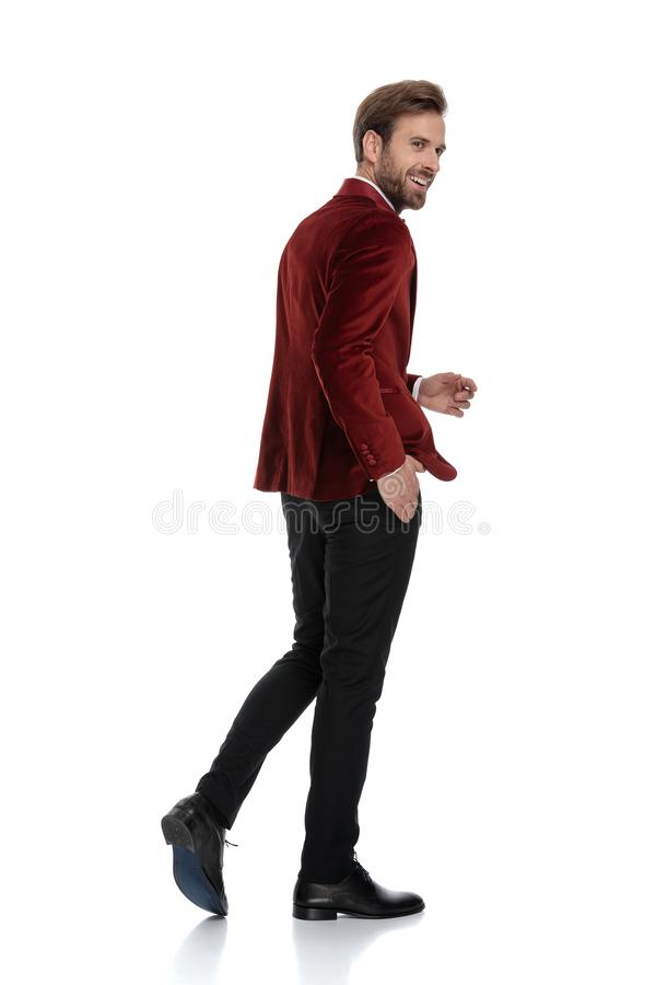 Happy young fashion man wearing red velvet tuxedo royalty free stock photography