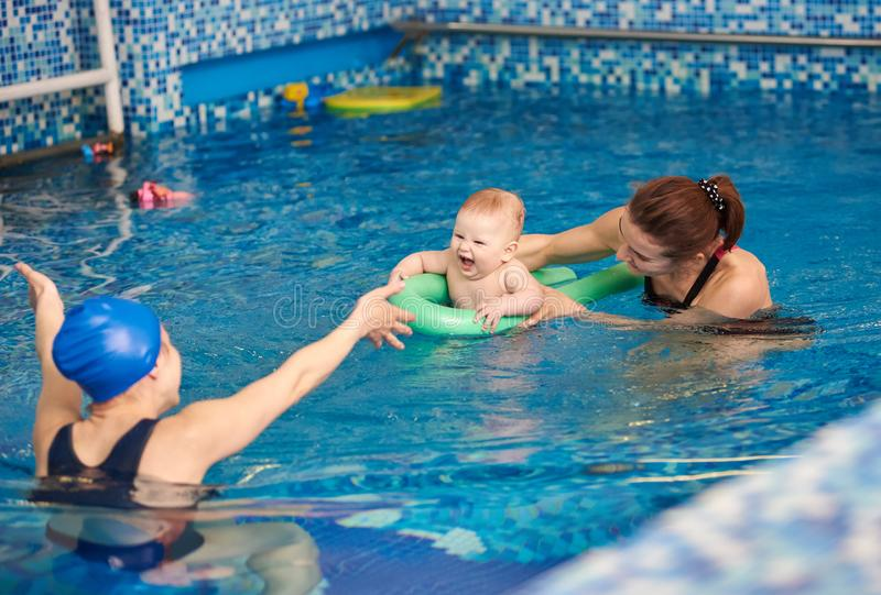 Happy mother and her son laughing baby boy having fun during swimming exercising with trainer in paddling swimming pool royalty free stock photography